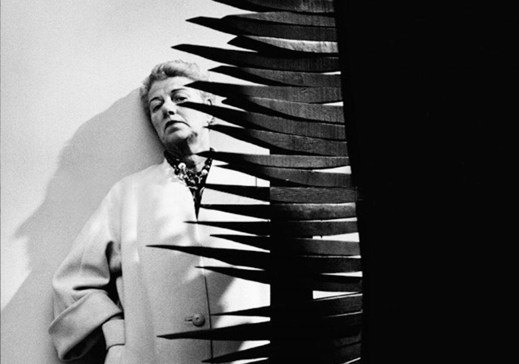 Peggy Guggenheim im weißen Mantel auf einer Ausstellung des Brooklyn Museum of Art Ende der 50er Jahre. Vor ihr steht eine Skulptur von Louise Nevelson. © Roloff Beny / Courtesy of National Archives of Canada