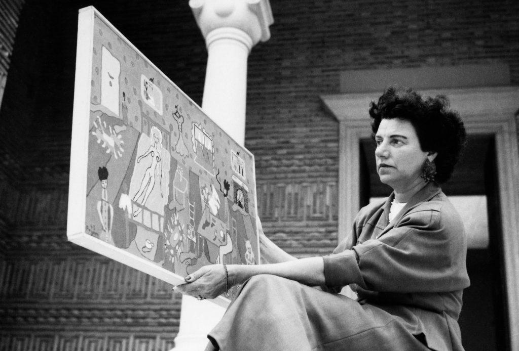 Peggy Guggenheim auf den Stufen des Griechischen Pavillons, in dem sie ihre Sammlung während der 24. Biennale in Venedig im Jahr 1948 ausstellte. In der Hand hält sie ein Gemälde ihrer Tochter Pegeen Vail (Interior, 1945). © Roloff Beny / Courtesy of National Archives of Canada