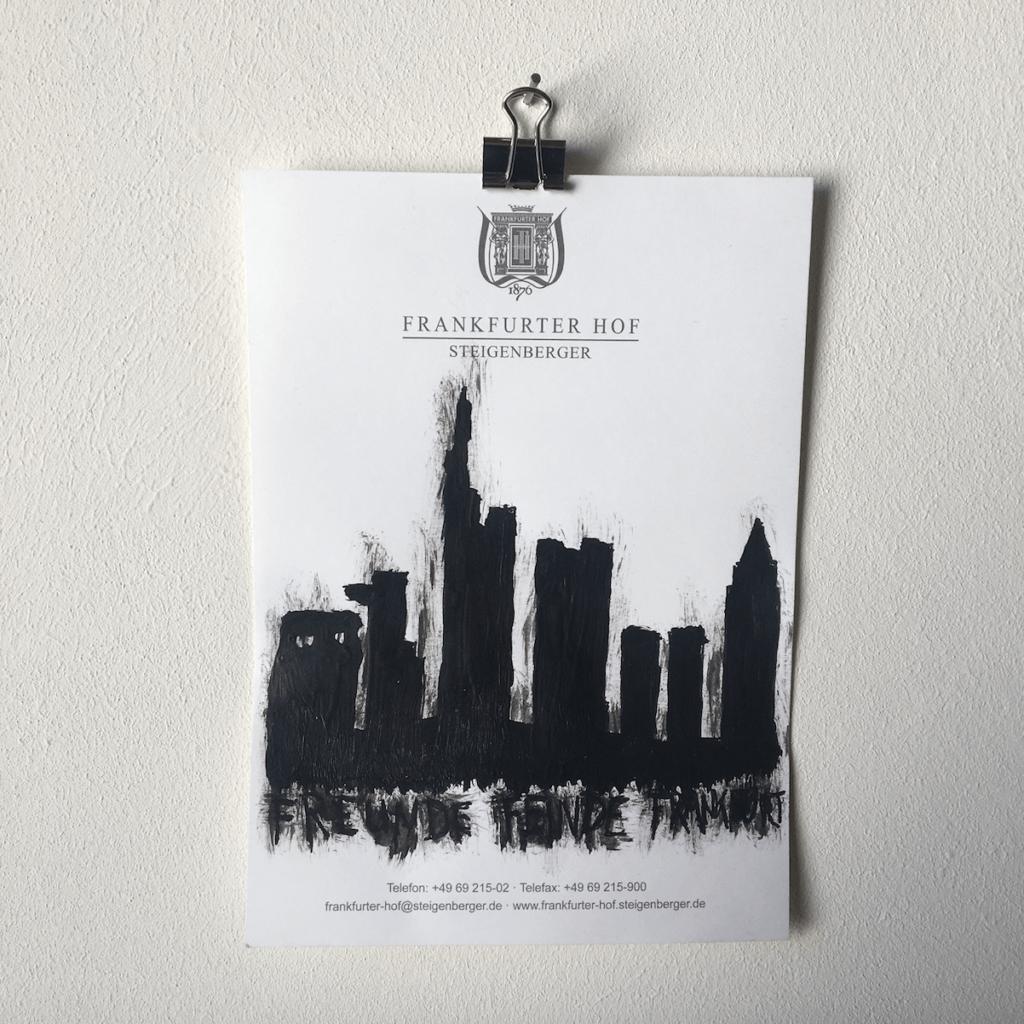 """Eine Zeichnung aus der Reihe """"Notizen aus der Edelquarantäne"""" von Künstler Nicholas Warburg. Auf einem Blatt vom Zettelblock des Hotels Frankfurter Hof ist die Skyline von Frankfurt am Main aufgemalt."""