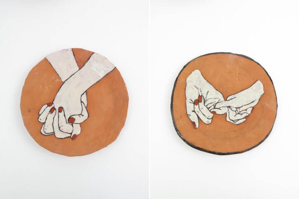 """Zwei Keramikarbeiten der Künstlerin Rose Eken. Beides sind Teller. Darauf zu sehen: Hände, die sich berühren. Die Arbeiten heißen """"Hands Holding""""."""