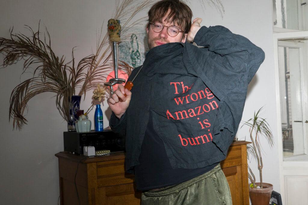 """Jacke aus der Merch-Kollektion von """"Arts of the Working Class"""". Das Kleidungsstück ist schwarz, darauf steht """"The wrong Amazon is burning""""."""