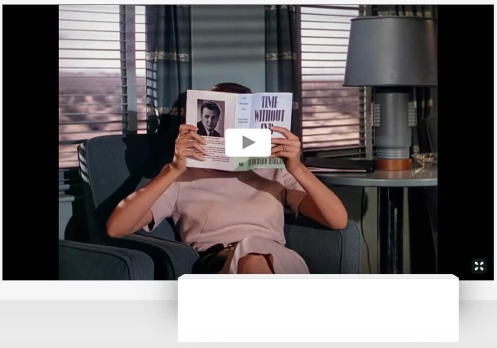 """Im Online Viewing Room von Videoart at Midnight ist Klaus vom Bruchs Videoarbeit """"Time Without End"""" hinter einer weißen Bank zu sehen. Eine Frau sitzt im Zug und liest. Dabei schläft sie ein."""