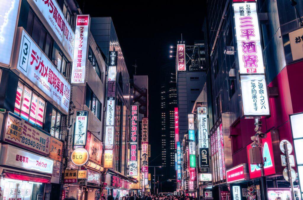 Tokios Stadtteil Shinjuku bei Dunkelheit. Links und rechts der vollen Straße überall Leuchtreklame.