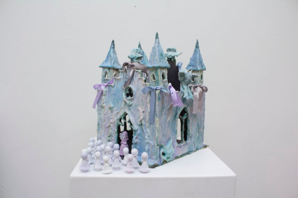 """Kunstwerk """"Feudal Castle"""" von Emma Pryde. Man sieht ein Keramikschloss in Zartlila. Im Eingang steht eine Priester-Figur, davor mehrere Engelsfiguren."""