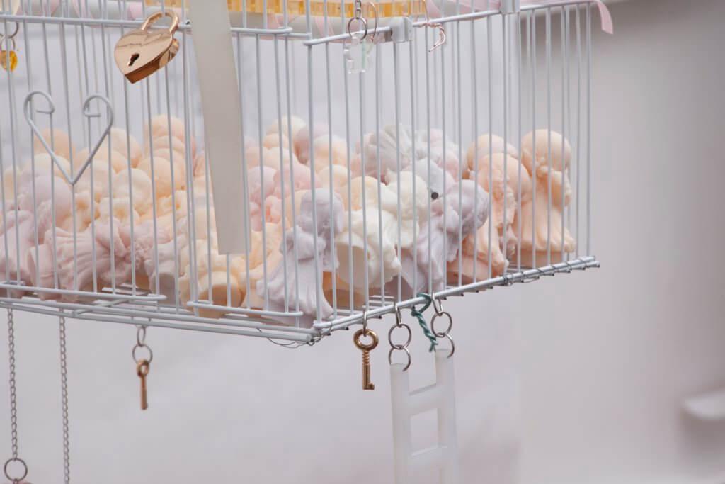 """Das Kunstwerk """"White Suburban Home"""" von Emma Pryde. Man sieht einen Vogelkäfig voller pastellfarbener Engelsfiguren. Am Käfig sind ein Schloss, Schlüssel und eine Leiter befestigt."""