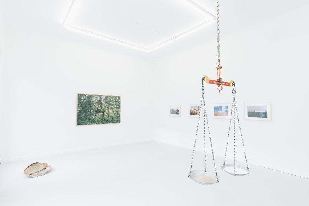 """Ausstellungsansicht """"A Year without the Southern Sun"""" in der XC.HuA Gallery. Im White Cube hängen Fotografien, auf dem Boden liegt eine Muschel, an der Decke hängt eine Wage."""