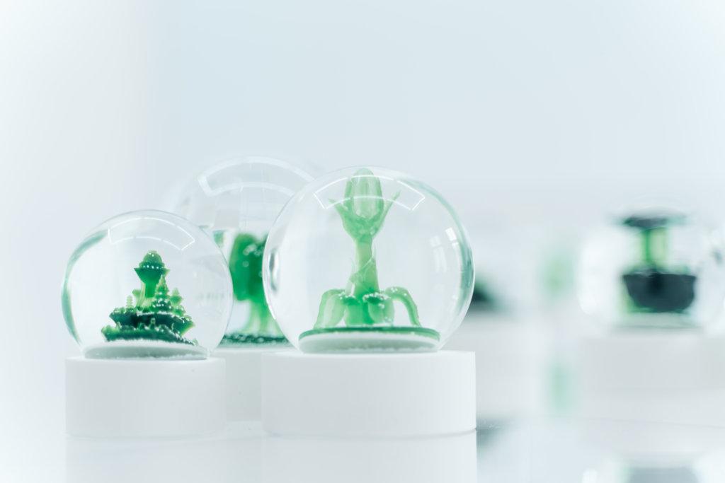Installation von Neda Saeedi. Mehrere Schneekugeln, in denen grüne Objekte zu erkennen sind.
