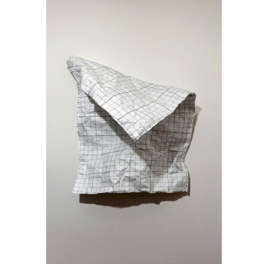 skulpturale Wandarbeit von Woo Yeong Chun. Man sieht ein zerknittertes, gerastertes stück Papier