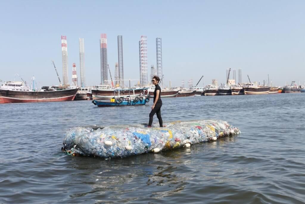 Die Künstlerin Tita Salina steht auf einer Insel aus Müll, die im Wasser eines Hafens treibt.