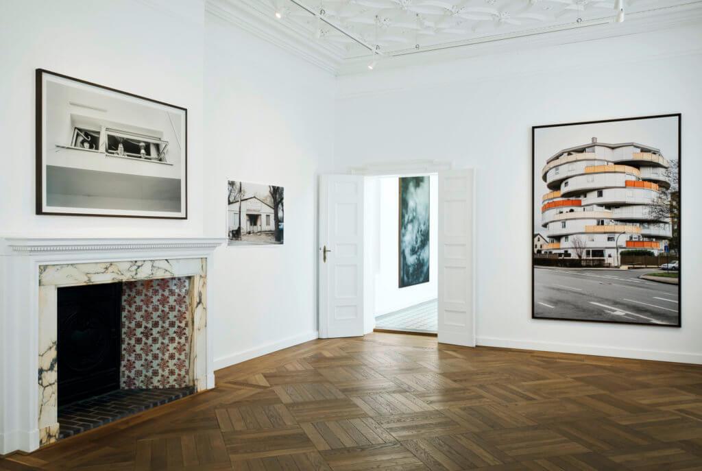 Ausstellungsansicht aus der Villa Schöningen. Ein Raum mit Parkettboden und Kamin, an den Wänden Fotografien.