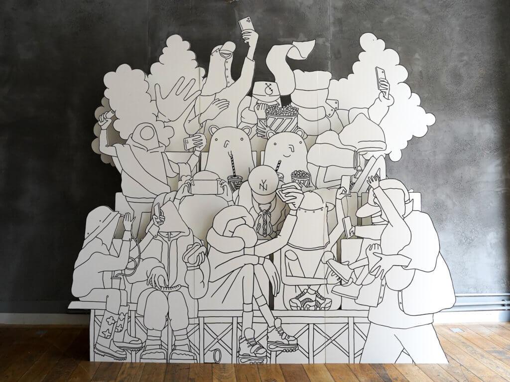 Die Genießer umrundet von Figuren als überdimensionale Figur aus Pappe