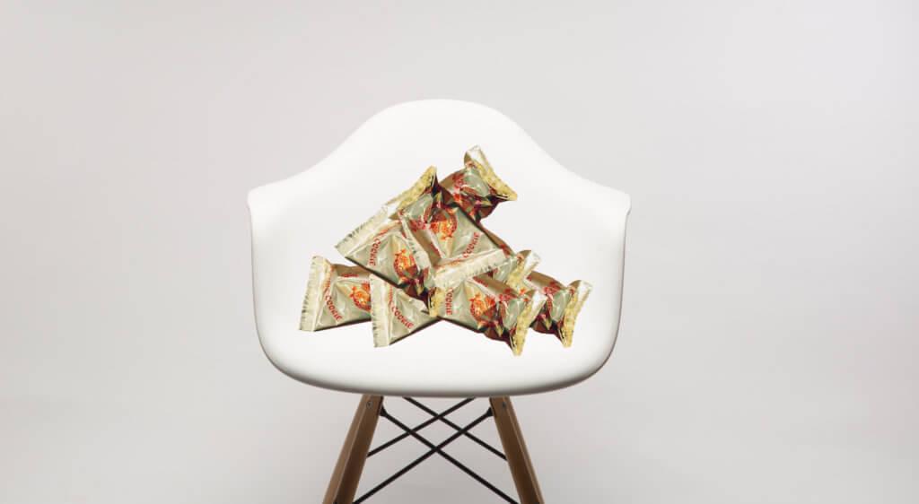 Ein weißer Eames-Chair auf dem Glückskekse gestapelt sind.
