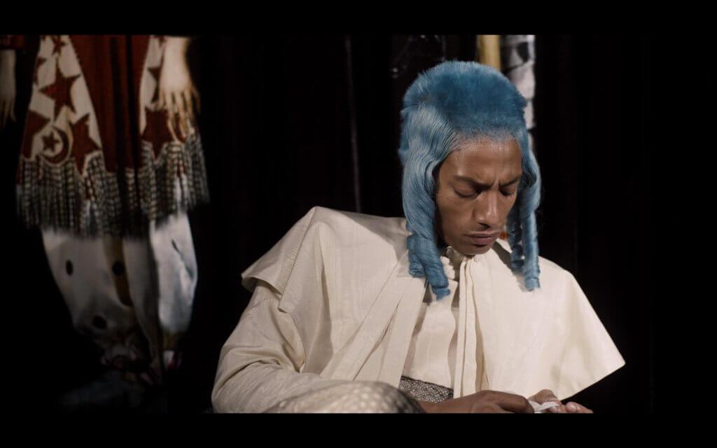 """Das Bild ist ein Filmstill aus Leila Hekmats Video """"Crocopazzo"""". Es zeigt den Performancekünstler MJ Harper in seinem Kostüm. Der Künstler trägt eine blaue Perücke und ein weißes Oberteil, der Bildausschnitt zeigt den Oberkörper inklusive Kopf. MJ Harper blickt nach unten auf seine Hände und scheint in Gedanken."""