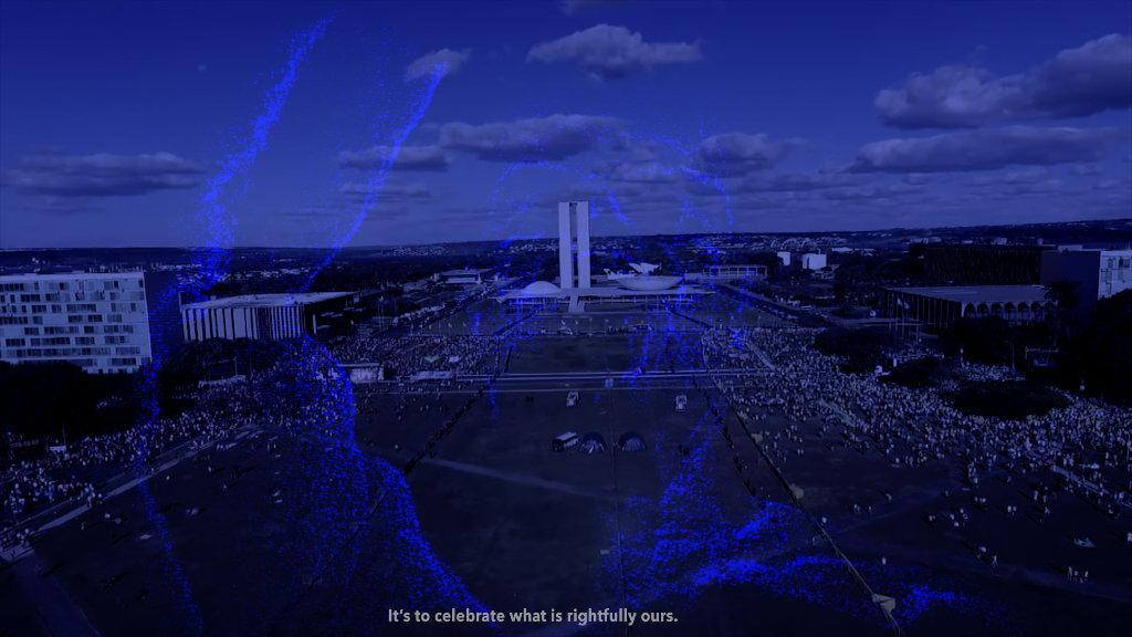 """Zu sehen ist eine blaustichige Aufnahme einer Stadt. Sie ist Teil der Videoarbeit """"Corpo Fechado"""" von Mario Pfeiffer. Auf dem Still ist der Text: """"It's to celebrate what is rightfully ours"""" zu lesen."""