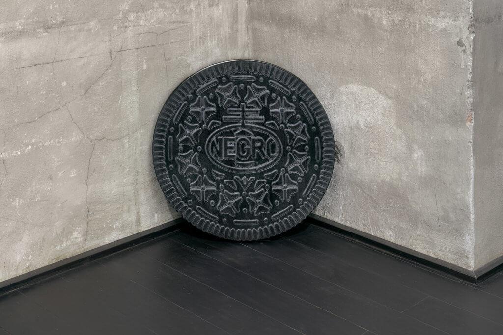 """Eine Arbeit des Künstlers Michael Sayles. Zu sehen ist ein kreisrundes Bild, das an einen Oreo-Keks erinnert. Statt des Markennamens ist """"NEGRO"""" zu lesen."""