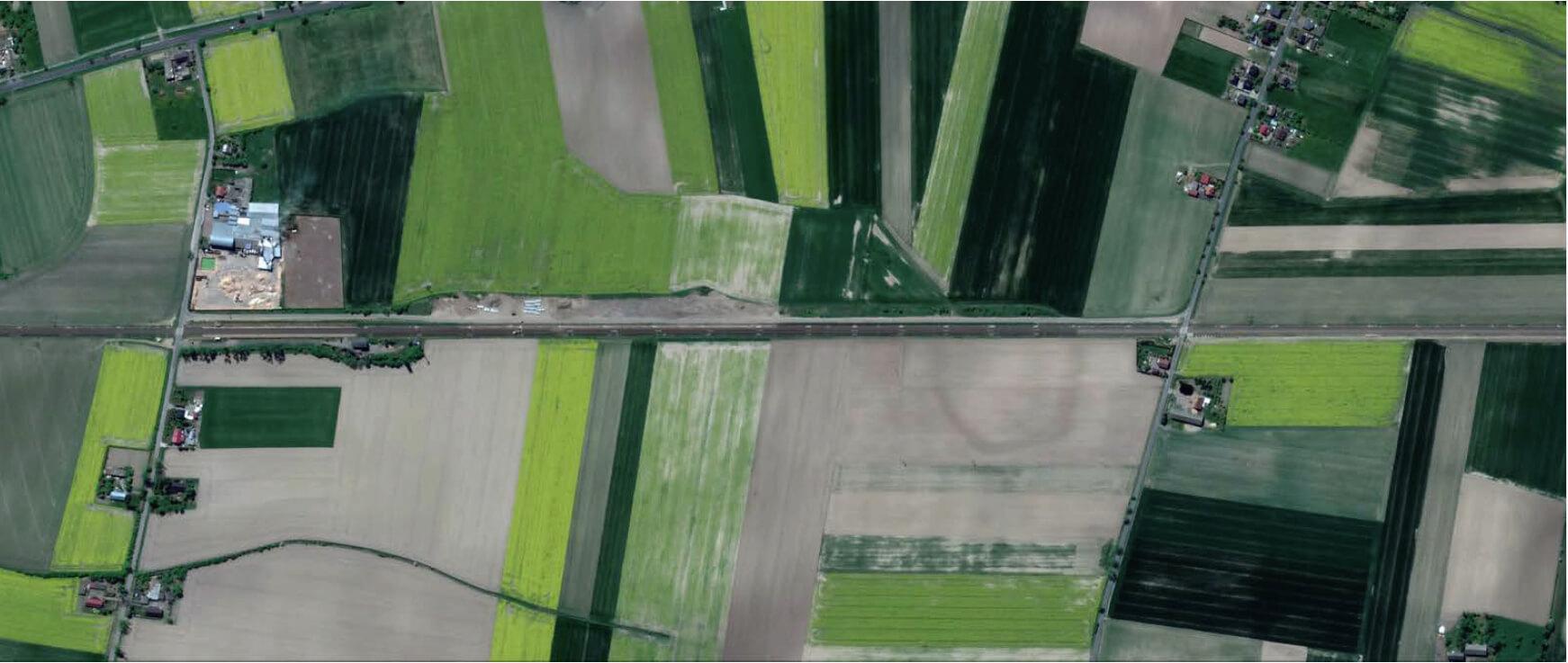 Satellitenaufnahme von Bahnstrecke durch Landschaft, strukturiert mit grünen und dunklen Feldern.