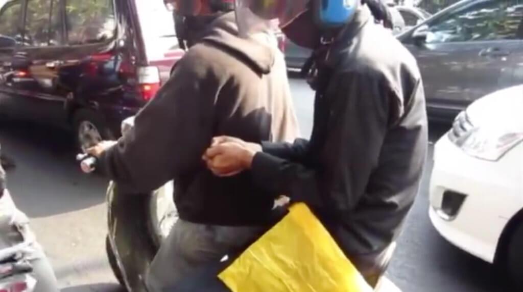 Zwei Personen auf einem Motorroller. Die hintere Person hält etwas in der Hand (den Fisch).