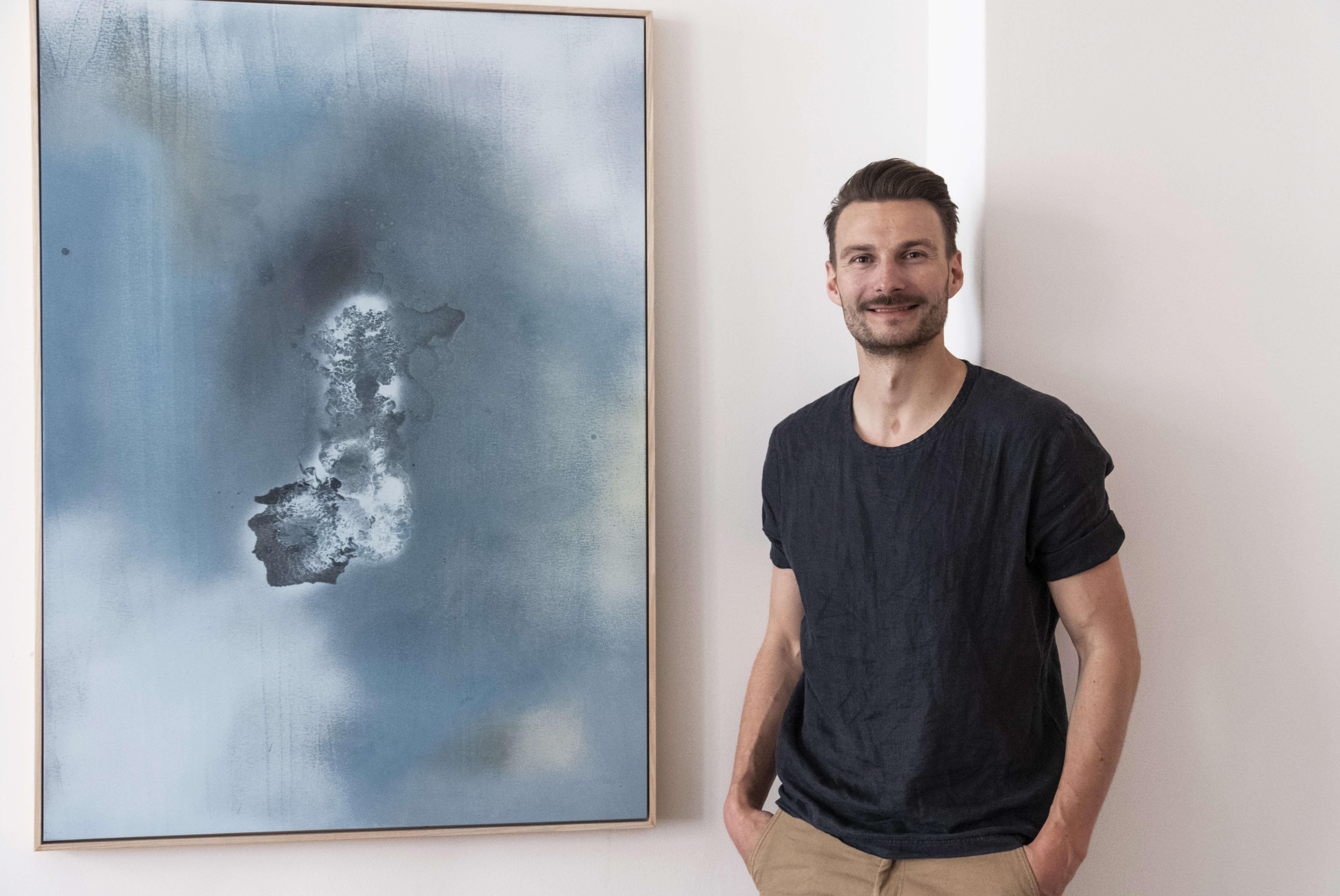Künstler Felix Schulze vor Gemälde