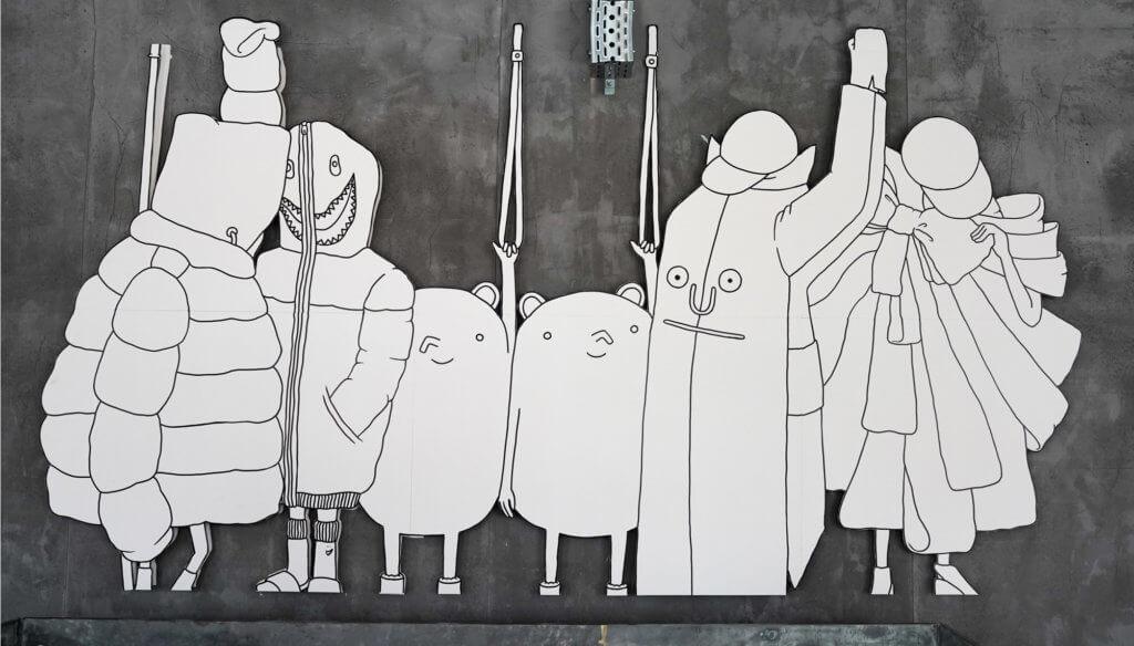 Die Genießer Figuren auf einer grauen Wand