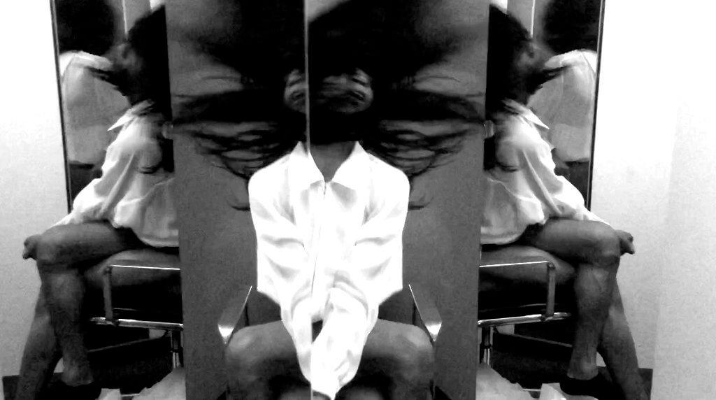 Das Bild zeigt den Performancekünstler MJ Harper bei einer Performance. Es ist eine dreifach-Ansicht mit Spiegel, der Künstler ist in zwei Seiten- und einer Frontalansicht zu sehen. Er trägt ein weißes Hemd und eine Langhaarperücke, durch eine starke Kopfbewegung befindet sich das Haar in der Luft. Das Foto ist eine schwarz-weiß Aufnahme.