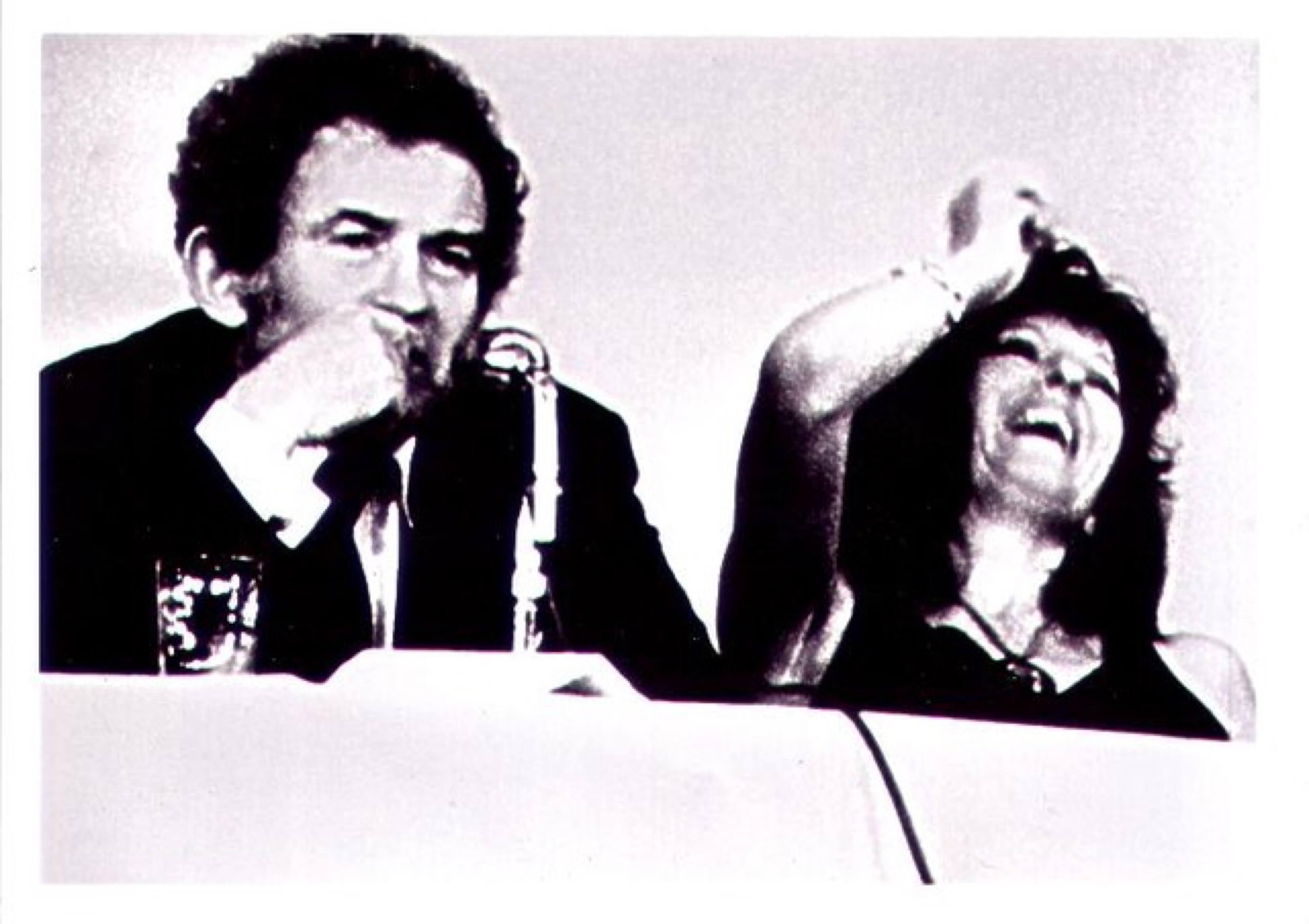 Filmstill in schwarz-weiß: Town Bloody Hell, 1979, Mann und Frau rauchen und lachen