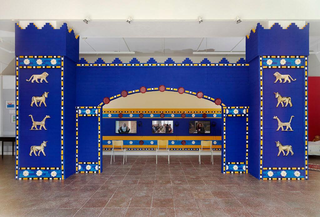 """Das Bild zeigt eine Ausstellung-Ansicht der Ausstellung """"Fasahat"""". Zu sehen ist eine Nachbildung des Ishtar-Tor mit drei Bildschirmen im Hintergrund. Das Tor hat eine kräftige blaue Farbe."""