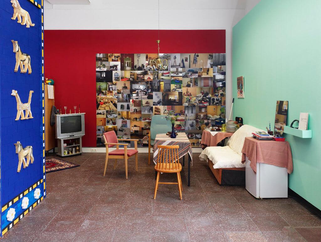 """Das Bild zeigt eine Ausstellung-Ansicht der Ausstellung """"Fasahat"""". Zu sehen ist eine Installation in Form einer Sitzgruppe, dahinter ist eine Fotowand zu sehen."""