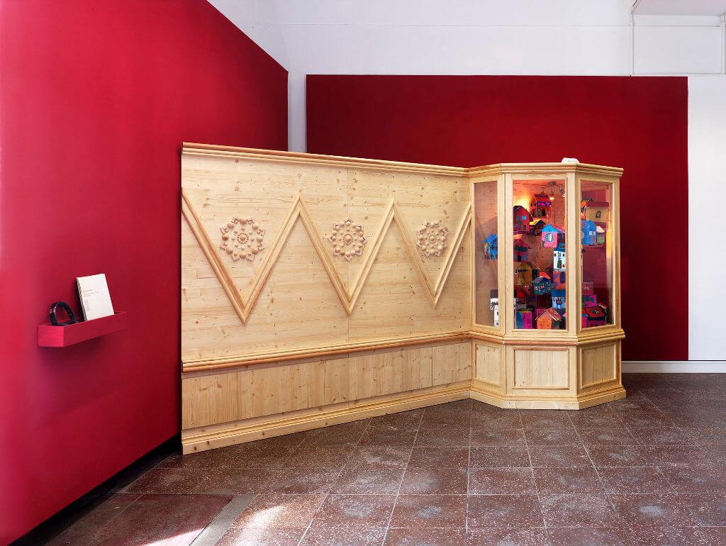 """Das Bild zeigt eine Ausstellung-Ansicht der Ausstellung """"Fasahat"""". Zu sehen ist eine verzierte Holzwand mit einer Vitrine an einem Ende. Die Vertäfelung steht vor einer roten Wand, es handelt sich um eine Installation."""