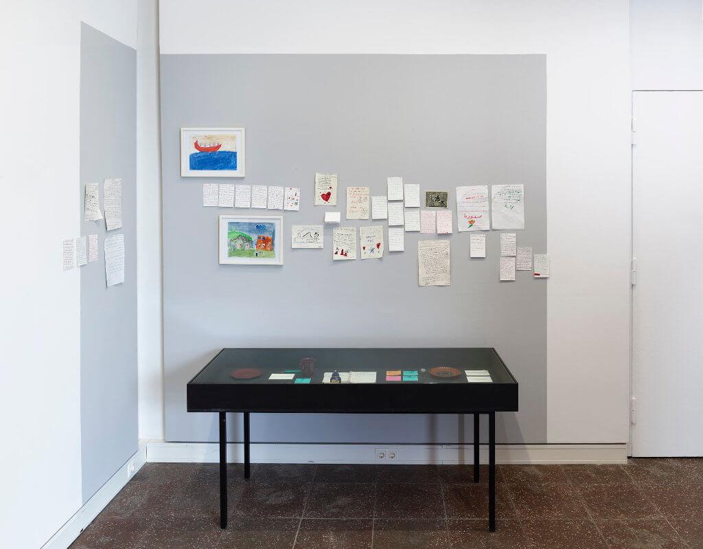 """Das Bild zeigt eine Ausstellung-Ansicht der Ausstellung """"Fasahat"""". Zu sehen ist eine Vitrine, darüber hängen Zeichnungen und Briefe der Ausstellungsteilnehmer."""