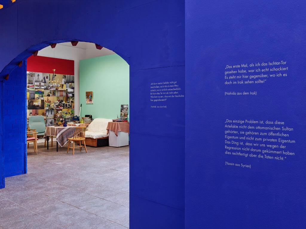 """Das Bild zeigt eine Ausstellung-Ansicht der Ausstellung """"Fasahat"""". Zu sehen ist die Rückwand des nachgebauten Ishtar-Tors in blauer Farbe mit Zitaten darauf gedruckt."""
