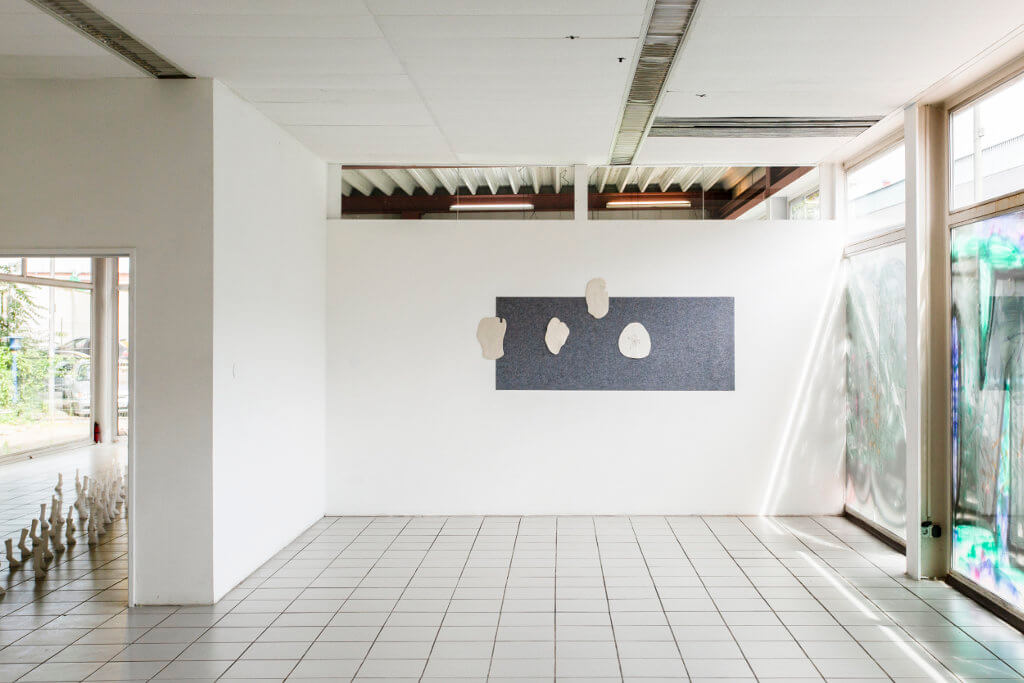 Das Bild zeigt eine Ausstellung-Ansicht.Frontal dem Betrachter zugewandt ist eine weiße Wand, an welcher ein Kunstwerk hängt. An der rechten Seite des Raumes ist eine Fensterfront, welche durch Farbe verdeckt ist, an der linken ist ein Durchgang zu sehen, welcher in einen weiteren Raum führt. Der Raum ist weiß gefliest und hat weiße Wände.