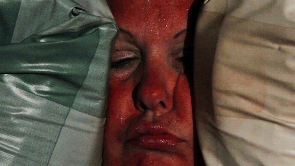 """Filmstill der Arbeit """"Squeeze"""". Das gerötete Gesicht einer Frau eingequetscht."""
