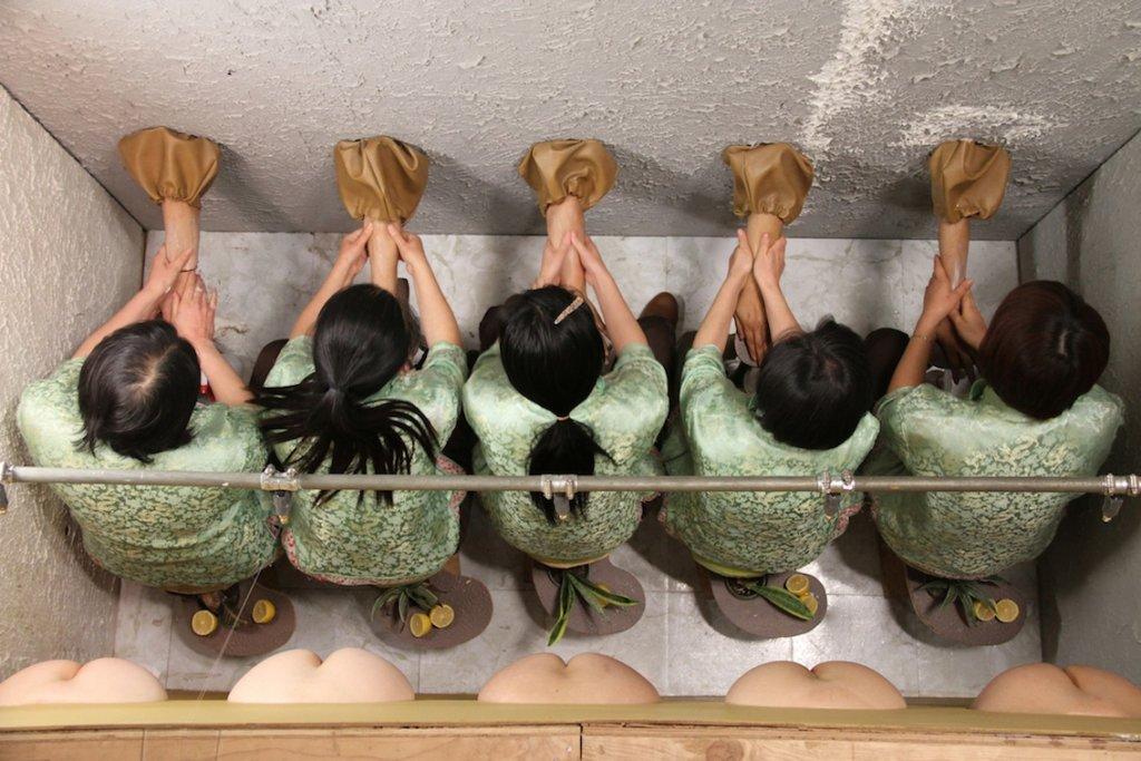"""Filmstill der Arbeite """"Squeeze"""" von Mika Rottenberg. Mehrere Frauen bei synchroner Arbeit."""