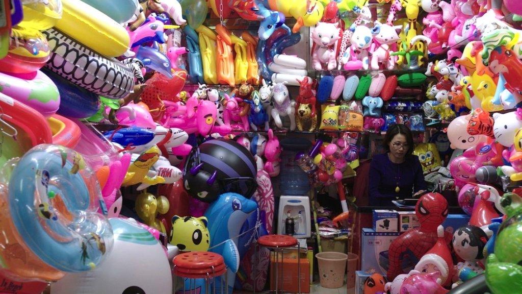 """Filmstill der Arbeite """"Squeeze"""". Ein Laden voller bunter Plastikschwimmtiere."""