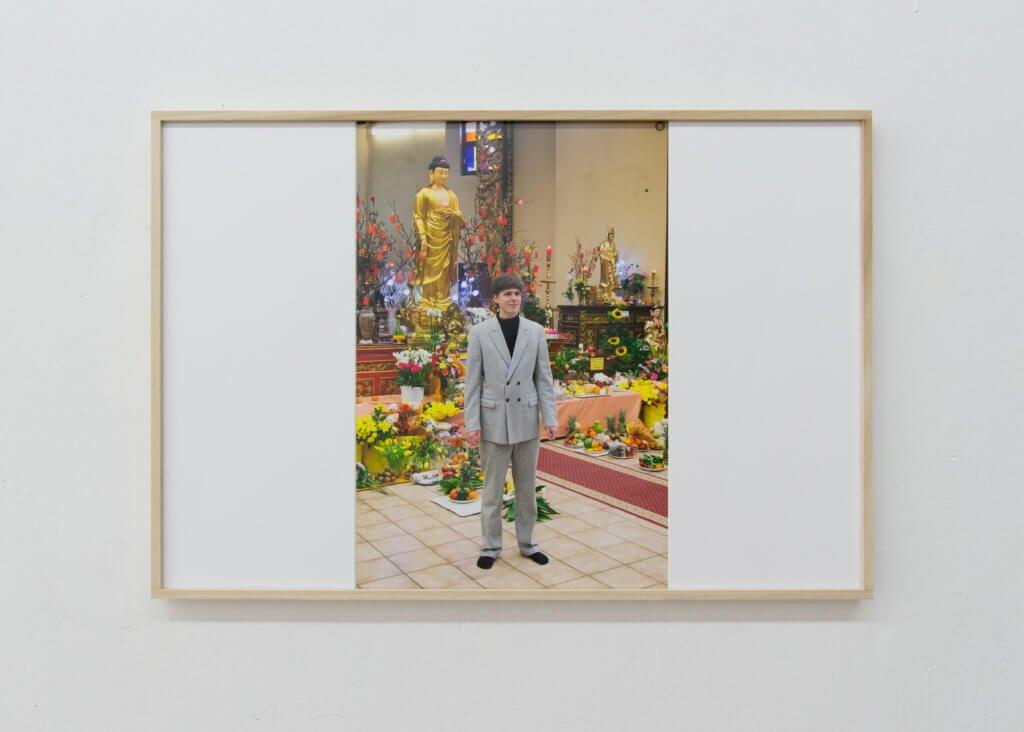 Fotografie von Niklas Taleb zeigt einen Mann im grauen Anzug vor Blumen und einer Buddha-Statue.