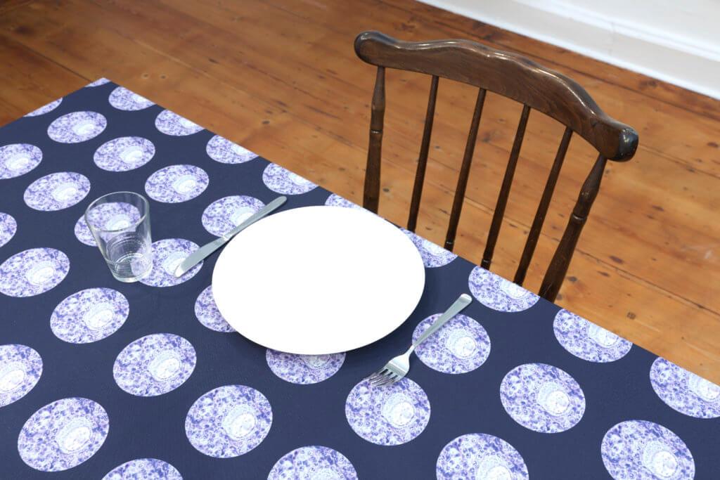 """Installationsansicht """"Hermaphrodit"""" im Syker Vorwerk. Ein Tisch mit gemusterter Tischdecke, Teller und Besteck."""