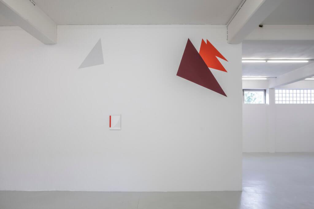 Ausstellungsansicht mit Arbeiten von Claudia de la Torre. Farbige Metallecken sind, ähnlich Eselsohren in einem Buch, an der Wand angebracht.