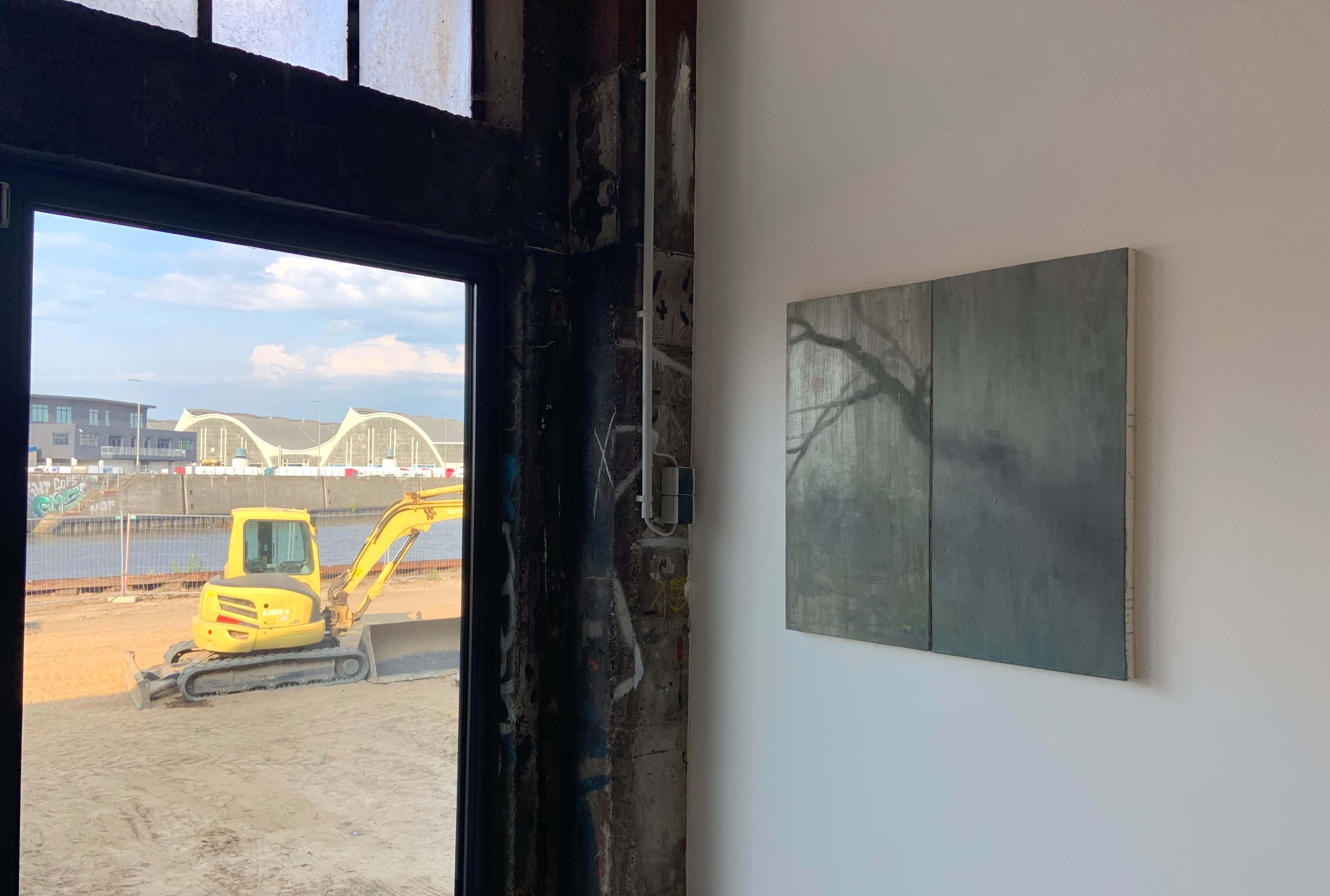 """Ausstellungsansicht Yang Kailiang """"画 Malerei"""" bei Tom Reichstein Contemporary. Blick us dem Fenster auf die Großmarkthallen und eine Baustelle. Gemälde von Yang Kailiang im Vordergrund."""