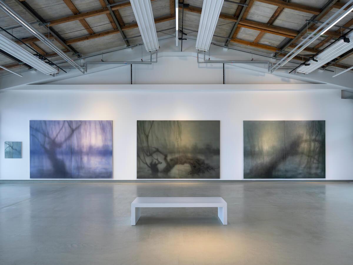 """Installationsansicht Yang Kailiang """"画 Malerei"""" bei Tom Reichstein Contemporary. Drei großformatige Bilder mit Baumdarstellungen in Grün- und Grautönen vor weißer Wand in umgewidmeter Industriearchitektur."""