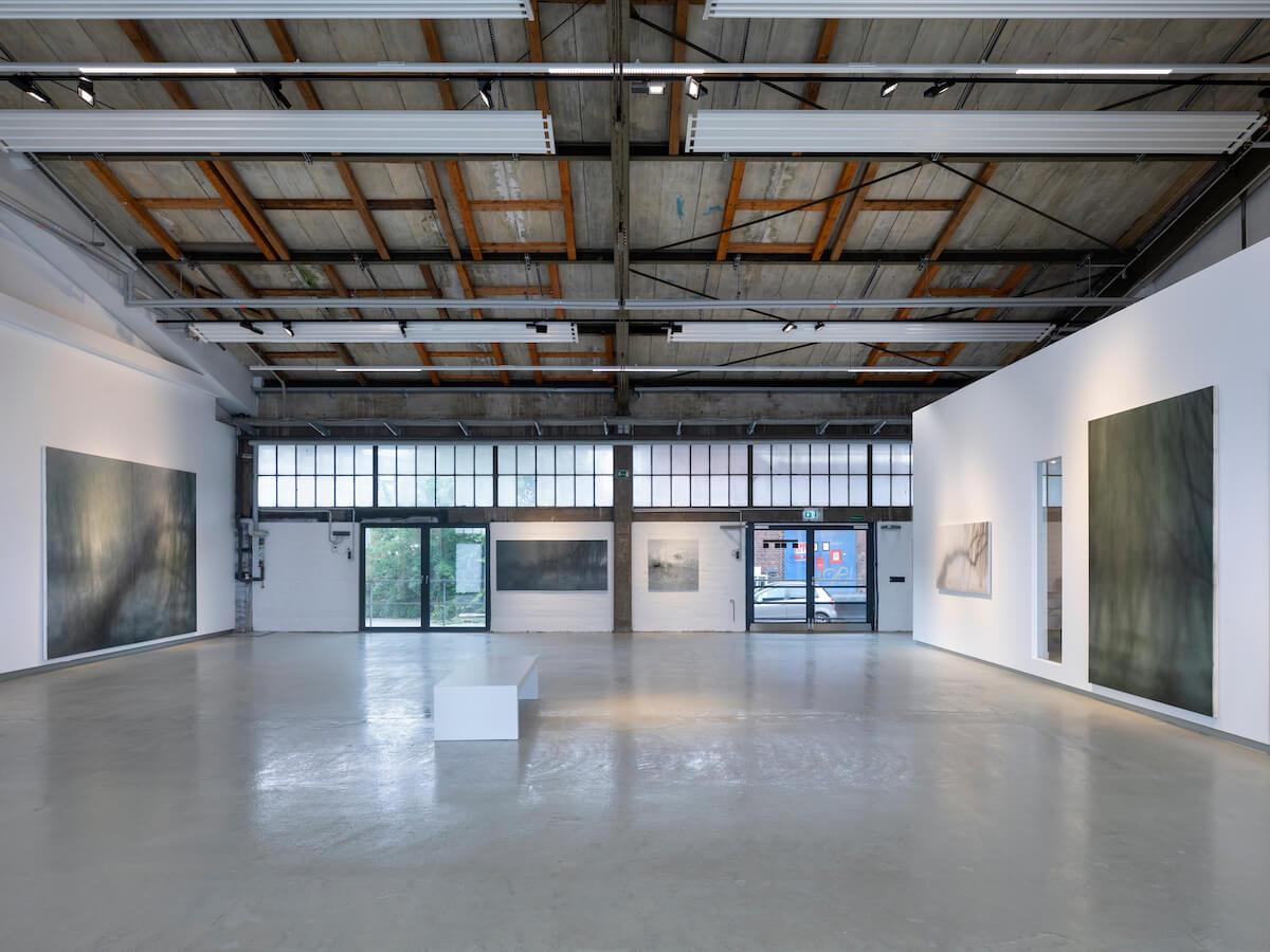 """Installationsansicht Yang Kailiang """"画 Malerei"""" bei Tom Reichstein Contemporary. Überblick über umgewidmeten Industrieraum mit großer Fensterfront, hellem Boden und Gemälden links und rechts an den Wänden."""