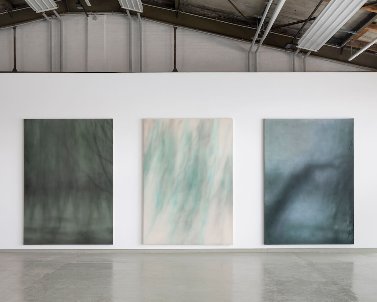 """Installationsansicht Yang Kailiang """"画 Malerei"""" bei Tom Reichstein Contemporary. Drei großformatige, hochkant-Bilder mit quasi-abstrakten Farbflächen in Grün- und Grautönen vor weißer Wand in umgewidmeter Industriearchitektur."""