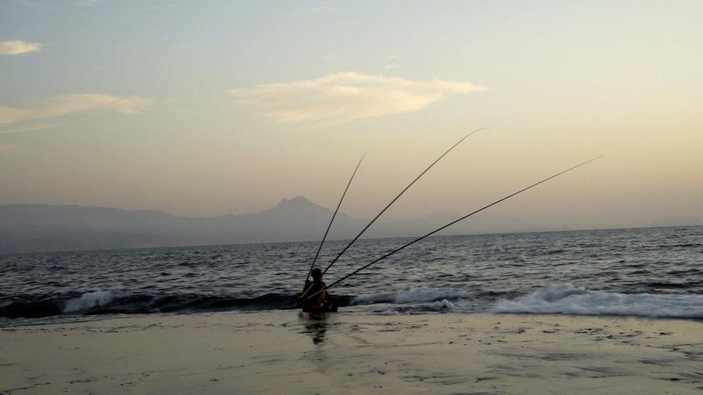 Filmstill aus 'Transmission Waves' von Judith Egger zeigt die Künstlerin mit ihrer Konstruktion aus Angelruten auf dem Rücken im Meer