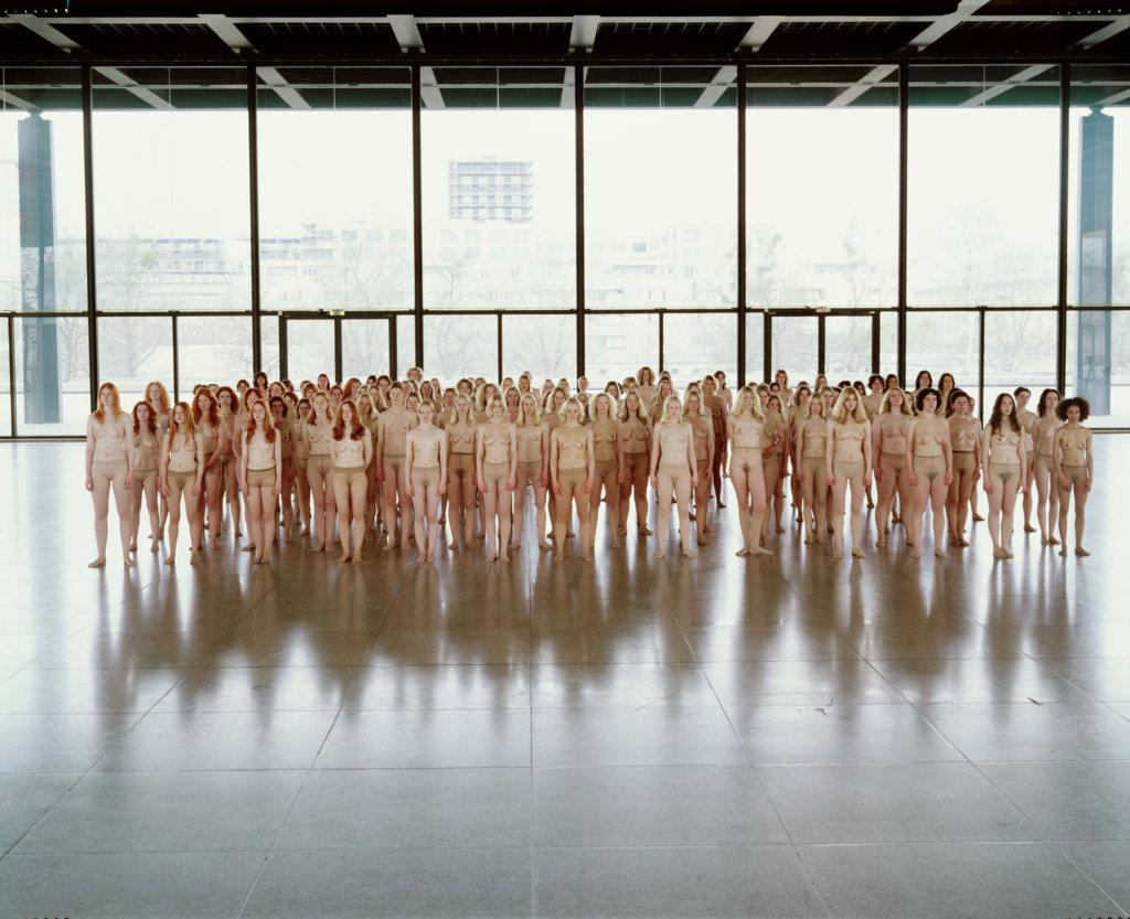 Viele Frauen stehen nur mit einer hautfarbenen Strumpfhose bekleidet nebeneinander für eine Installation von Vanessa Beecroft.