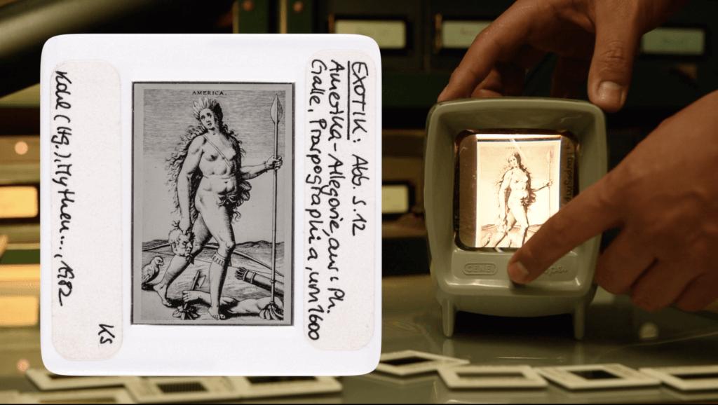 Ein Dia mit einem Holzstich einer unbekleideten Frau, dahinter weitere Dias und ein Bildschirm