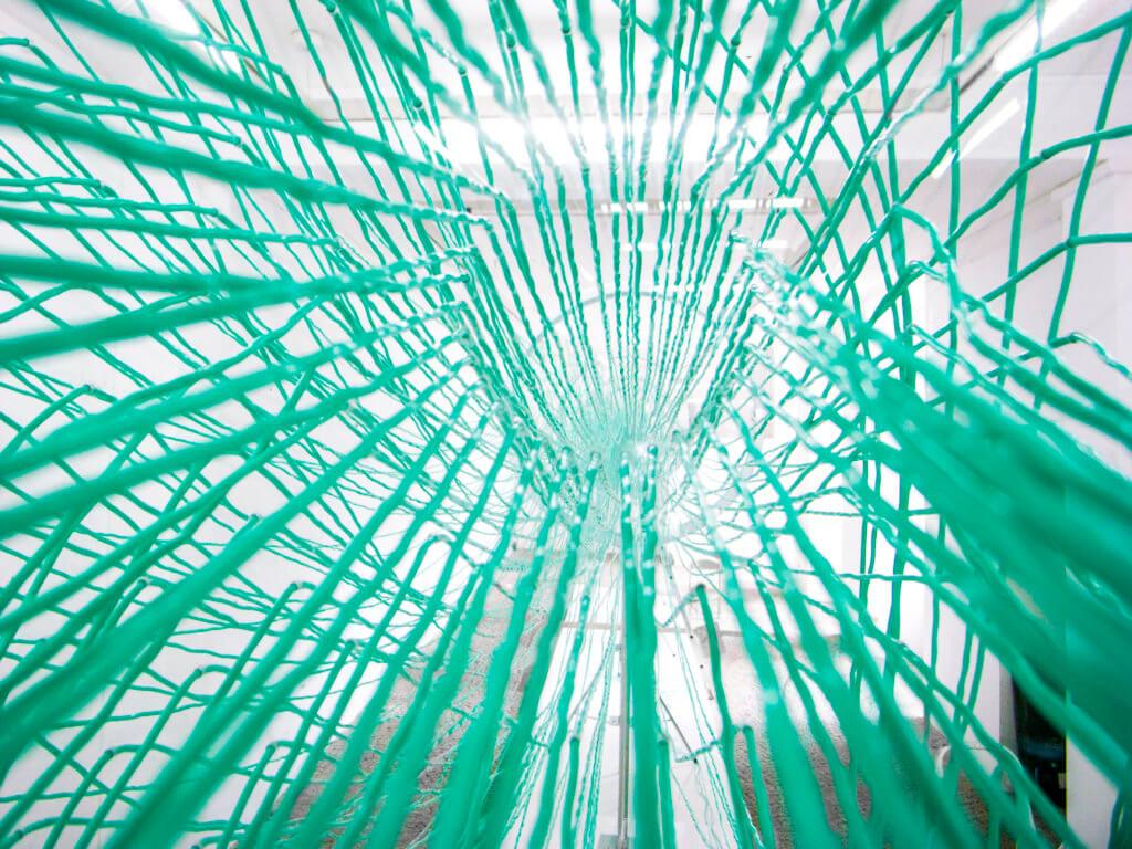 Blick durch ein filigranes Netz in einen Galerieraum.