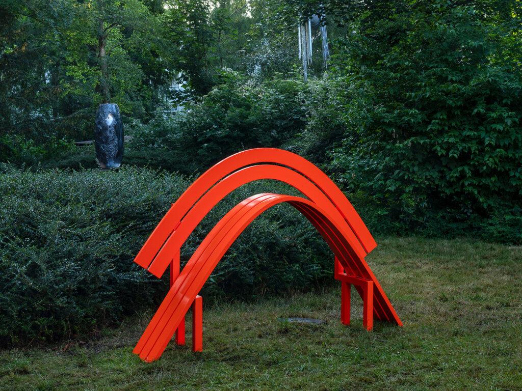 Ansicht Garten der Gegenwart, Jeppe Hein: Modified Social Bench NY #14, 2015: Eine stark nach oben gebogene, leuchtorangene Parkbank