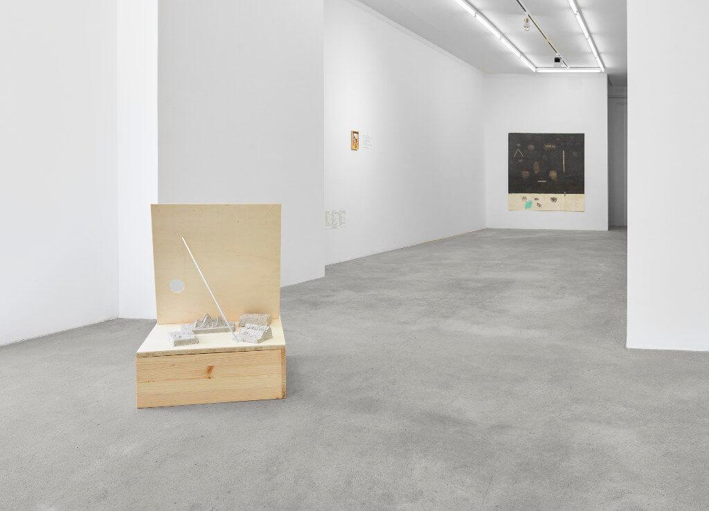 """Das Bild zeigt eine Ausstellungsansicht der Ausstellung """"Crust"""" von Goutam Ghosh. Zu sehen sind zwei Arbeiten, ein quadratisches Objekt aus Holz im Vordergrund sowie eine an der Wand hängende Arbeit in überwiegend schwarzer Farbe an der Stirnwand der Galerie im Hintergrund des Bildes."""