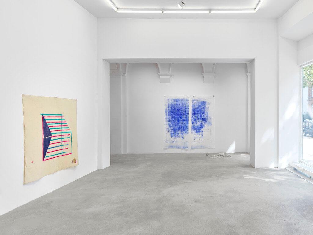 """Das Bild zeigt eine Ausstellungsansicht der Ausstellung """"Crust"""" von Goutam Ghosh. Zu sehen sind zwei an der Wand hängende Arbeiten, sowie der Galerieraum zur Straße hin."""