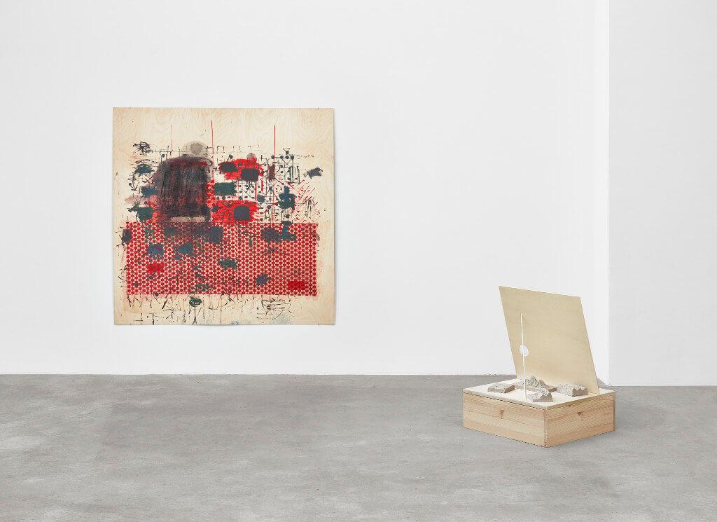 """Das Bild zeigt eine Ausstellungsansicht der Ausstellung """"Crust"""" von Goutam Ghosh. Zu sehen sind zwei Werke, eine Arbeit auf Leinwand in überwiegend roter und schwarzer Farbe, sowie ein Quadratisches Objekt aus Holz, welches auf dem Boden steht."""