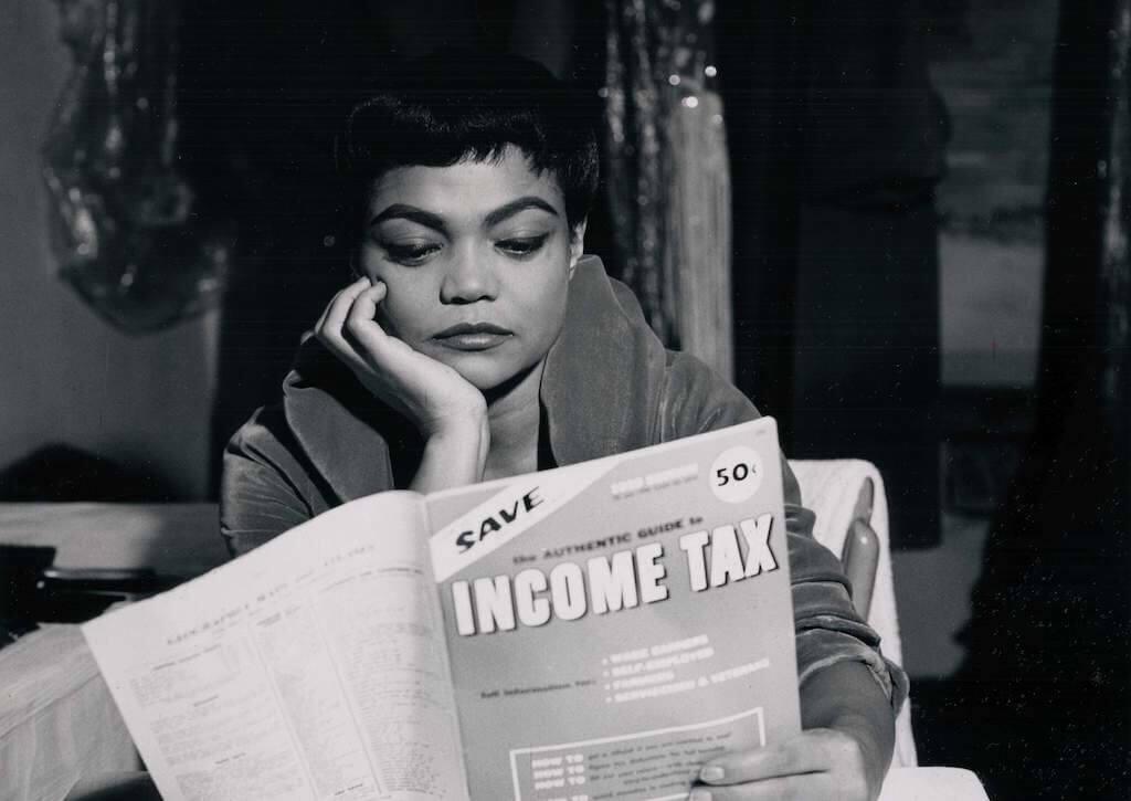 Man sieht eine afroamerikanische Frau lesend. Sie beschäftigt sich mit der Einkommenssteuer.